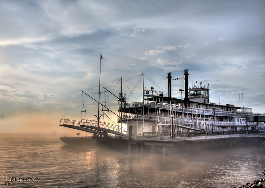 The Natchez paddleboat docked on the Mississippi just behind the French Quarter at dawn.